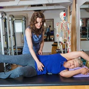 Mary Gorman working with a client on the table in The Movement Studio.