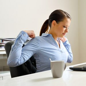 Woman at chair looking stiff and uncomfortable