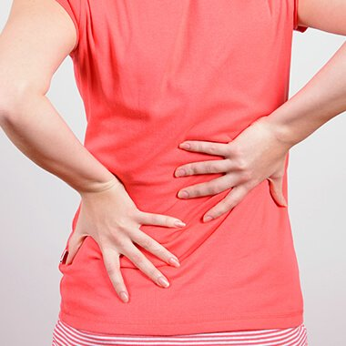 sciatics - back of woman with hands indicating lower back pain